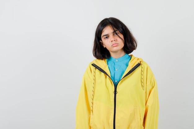 Klein meisje poseren terwijl ze in shirt, jas staat en er zelfverzekerd uitziet. vooraanzicht.