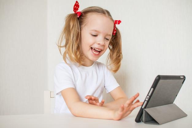 Klein meisje praat online. thuisonderwijs. afstand leren. online bellen met vrienden.