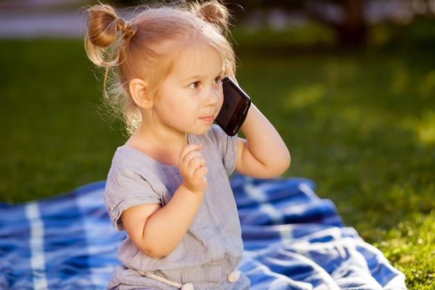 Klein meisje praten aan de telefoon in het park