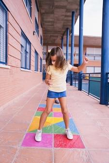 Klein meisje rent en springt op het schoolplein met gezichtsmasker tijdens de covid-pandemie. terug naar school tijdens de covid-pandemie