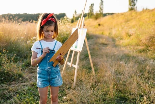 Klein meisje schildert buiten foto