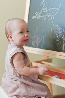 Klein meisje schildert op het bord