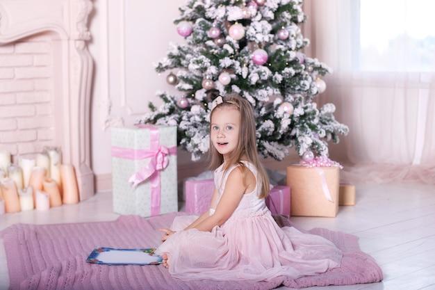 Klein meisje schrijft een brief aan de kerstman in de buurt van de kerstboom