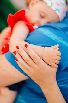 Klein meisje slaapt in de armen van haar vader, moeder houdt de baby bij het handvat