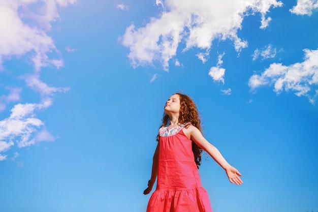 Klein meisje sloot haar ogen en ademt de frisse lucht in het park.