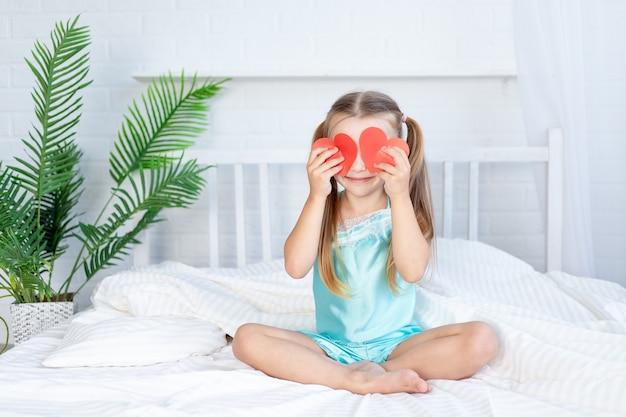 Klein meisje sloot haar ogen met harten die thuis op het bed op een wit katoenen bed zaten en lief lachten, het concept van valentijnsdag