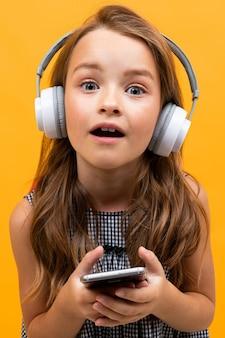 Klein meisje smartphone houden en hoofdtelefoon dragen