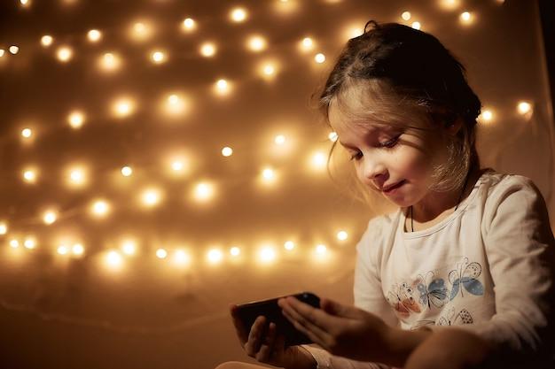 Klein meisje smartphone spelen in de kamer, portret van een meisje in de avond in een donkere kamer met slingers met telefoon in de hand