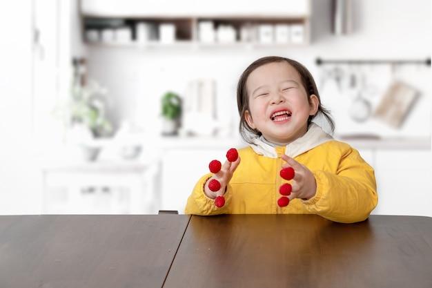 Klein meisje speelde met frambozen op haar vingers