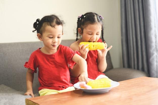 Klein meisje speelt en eet maïs thuis, aziatisch schattig meisje happy kids food concept