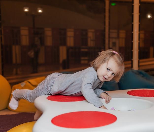 Klein meisje speelt in het kinderentertainmentcentrum