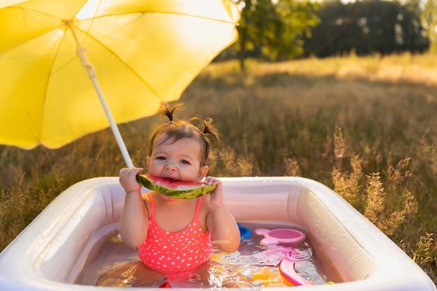 Klein meisje speelt in het opblaasbare zwembad.