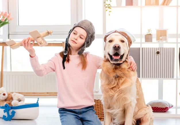 Klein meisje speelt in vliegtuigpiloot met golden retrieverhond