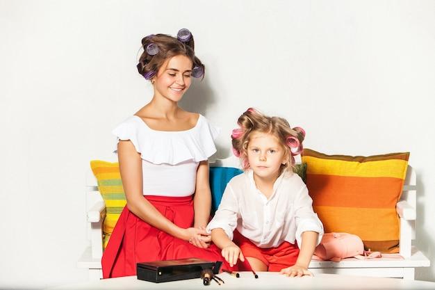 Klein meisje speelt met de make-up van haar moeder