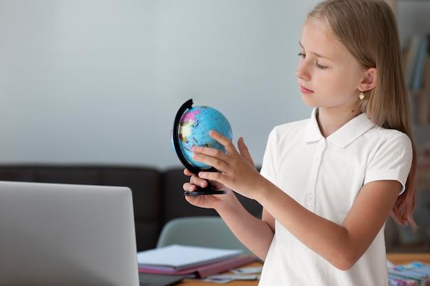 Klein meisje speelt met een aardbol