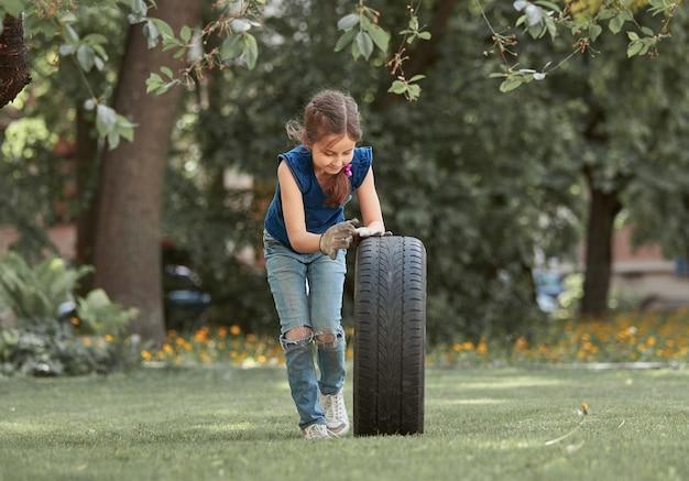 Klein meisje speelt met een autoband op de speelplaats in de buurt van het huis. stadsleven