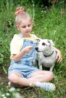 Klein meisje speelt met een hondenras jack russell terrier