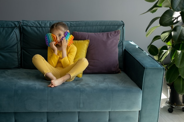 Klein meisje speelt met een modern pop-it-speelgoed zittend op een bank met geel kussen