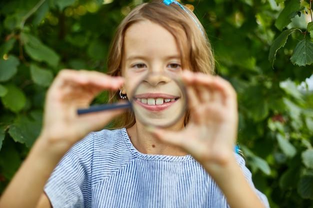 Klein meisje speelt met een vergrootglas in haar achtertuin en trekt gezichten