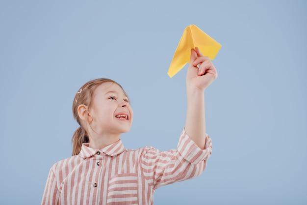 Klein meisje speelt met gele papieren vliegtuig geïsoleerd op blauwe achtergrond kopie ruimte