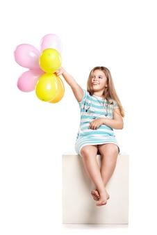 Klein meisje speelt met kleurrijke ballonnen op een witte achtergrond