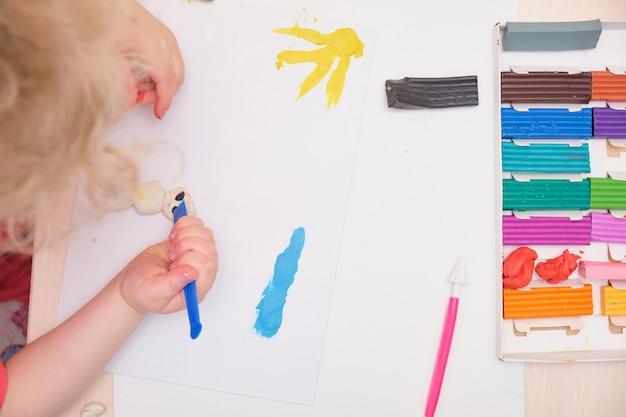 Klein meisje speelt met kleurrijke boetseerklei op tafel. home onderwijsspel met klei. vroeg ontwikkelingsconcept dat het kind beeldhouwt uit plasticine