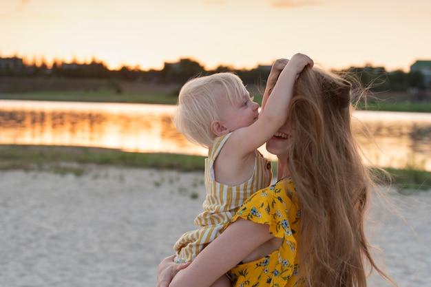 Klein meisje speelt met moeders haar. portret in beweging moeder en kind op rivier en zonsondergang.