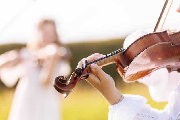 Klein meisje speelt viool buiten met tuin op de achtergrond op zonnige zomerdag