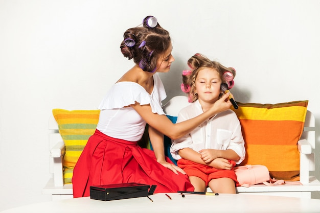 Klein meisje spelen met de make-up van haar moeder