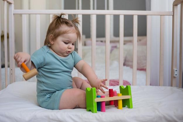 Klein meisje spelen met educatief speelgoed in babywieg in slaapkamer