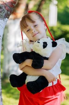 Klein meisje spelen met een speelgoedpanda in het park in de zomer. hoge kwaliteit foto
