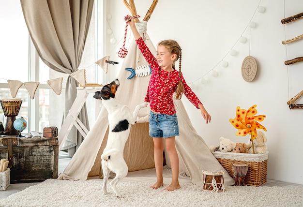 Klein meisje spelen met gladde fox terrier in kinderkamer