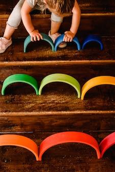 Klein meisje spelen met waldorf montessori regenboog van verschillende kleuren