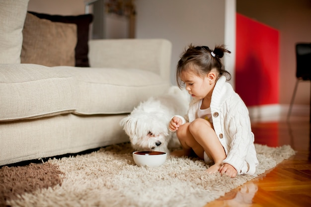 Klein meisje spelen met witte hond in de kamer