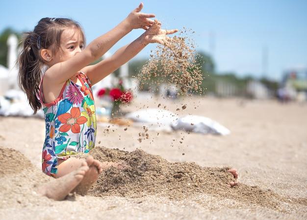 Klein meisje spelen met zand op het strand. een vrolijk kind. het concept van zomervakantie.