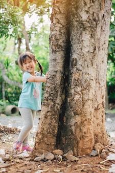 Klein meisje spelen onder de grote boom. concept voor de natuur, het broeikaseffect en de dag van de aarde.