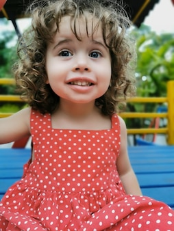 Klein meisje spelen op de speelplaats camera kijken en lachen.