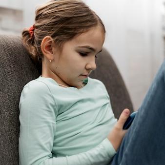 Klein meisje spelen op een smartphone binnenshuis