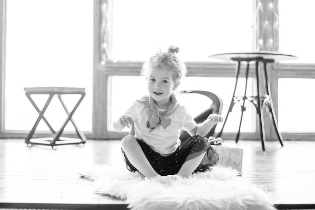 Klein meisje spelen zittend op het tapijt in de woonkamer. het concept van een gelukkige jeugd