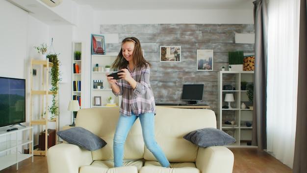 Klein meisje springt op de bank in de woonkamer terwijl ze videogames speelt op haar telefoon.
