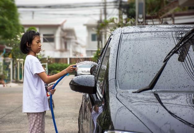 Klein meisje spuiten een auto met een waterslang een auto wassen
