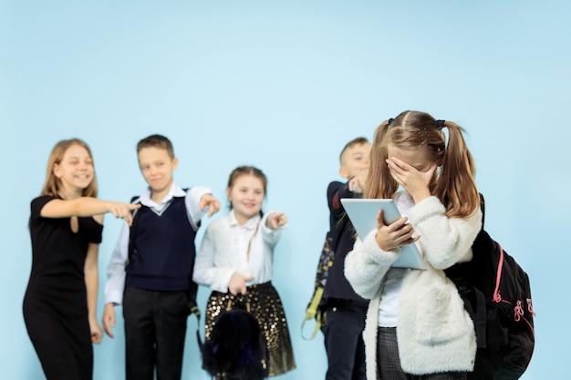 Klein meisje staat alleen en lijdt aan pesterijen terwijl kinderen spotten. triest jong schoolmeisje zittend op studio tegen blauwe achtergrond.