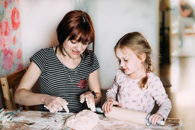 Klein meisje staat in de keuken helpt moeder het deeg met het hele gezicht in bloem te bereiden