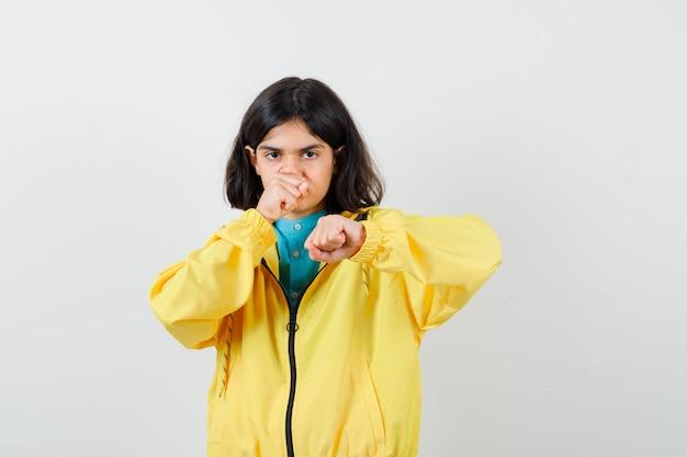 Klein meisje staat in de strijd pose in shirt, jas en ziet er zelfverzekerd uit. vooraanzicht.