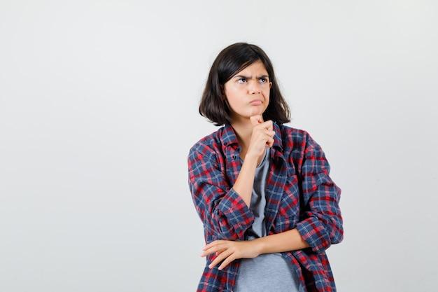 Klein meisje staat in denkende pose in geruit hemd en kijkt peinzend, vooraanzicht.