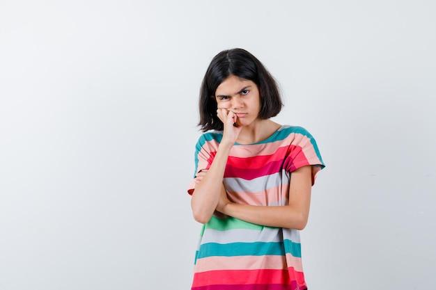 Klein meisje staat in denkende pose in t-shirt en kijkt peinzend, vooraanzicht.