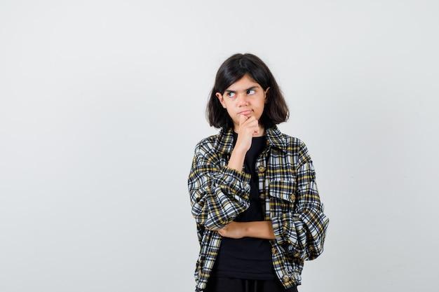 Klein meisje staat in denkende pose in t-shirt, jas en kijkt peinzend, vooraanzicht.