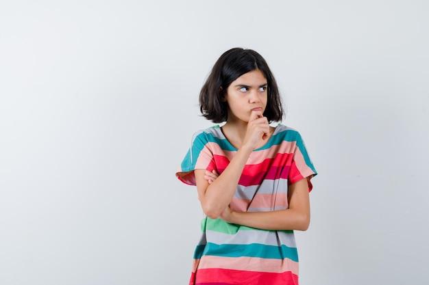 Klein meisje staat in denkende pose in t-shirt, spijkerbroek en kijkt peinzend. vooraanzicht.