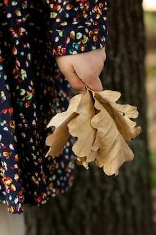 Klein meisje staat in een stadspark en houdt een gegoten eik vast. herfstwandelingen.