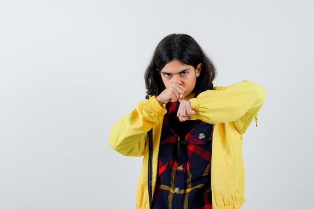 Klein meisje staat in gevecht pose in geruit hemd, jas en ziet er hatelijk uit. vooraanzicht.